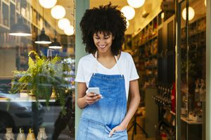 Young woman using phone in front of shop