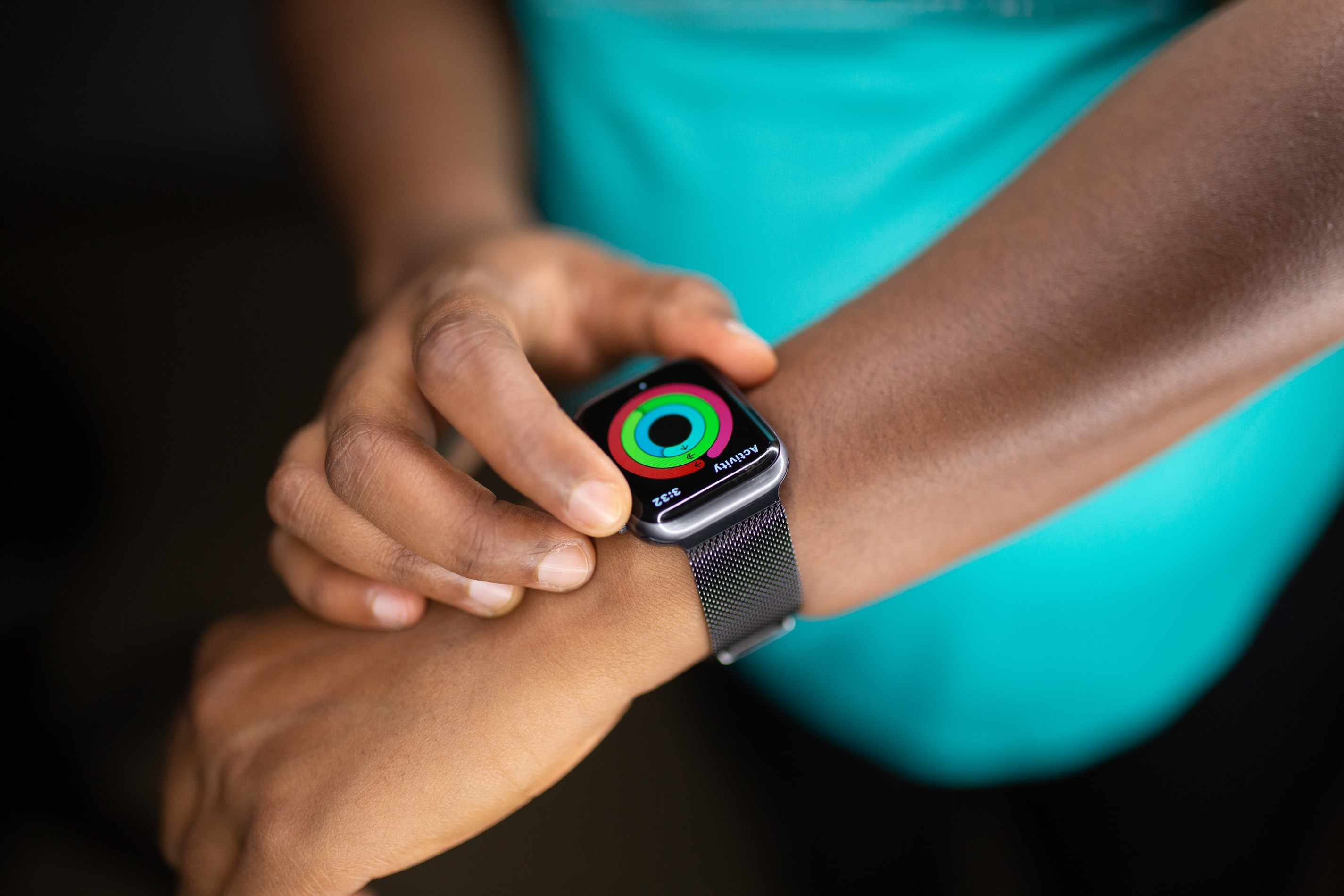 person wearing an Apple Watch and checking their activity rings
