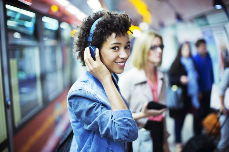 young woman listening to headphones in train station