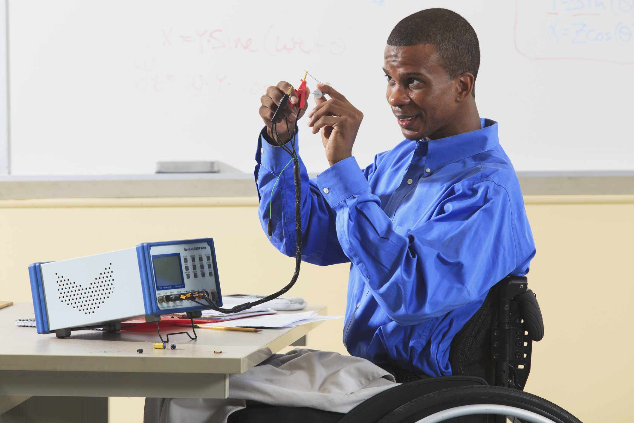 Engineering student in wheelchair connecting capacitor to LCR impedance meter