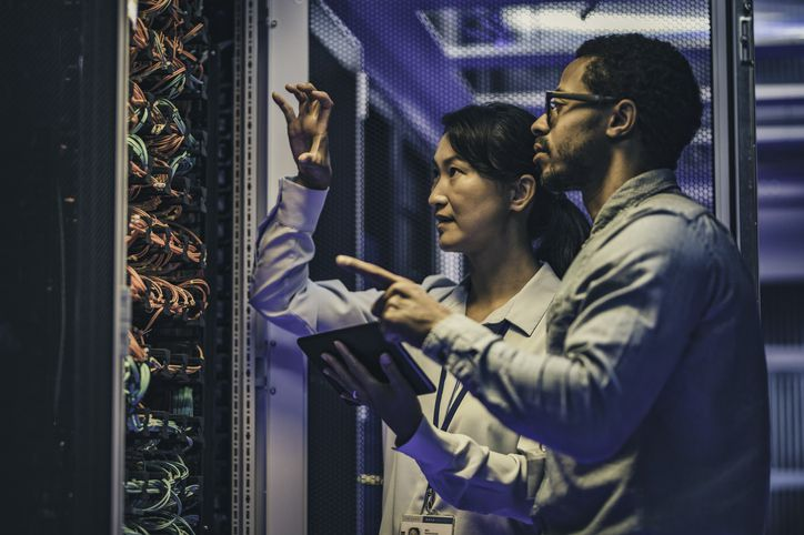 Side view of a female IT engineer explaining network connections in a server to a novice technician