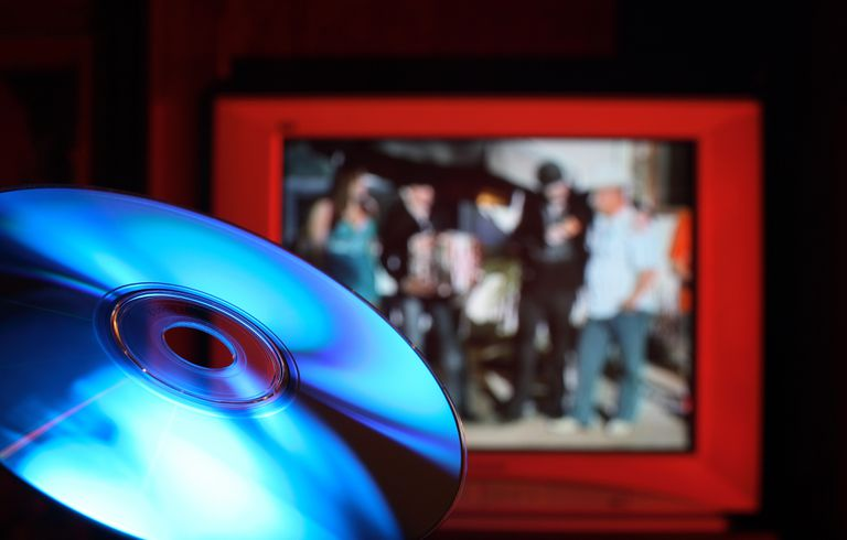 a Blu-Ray disc in foreground with television blurry in background