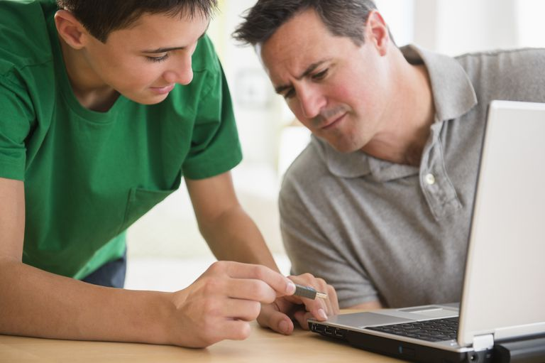 Caucasian son showing father how to use USB stick in laptop