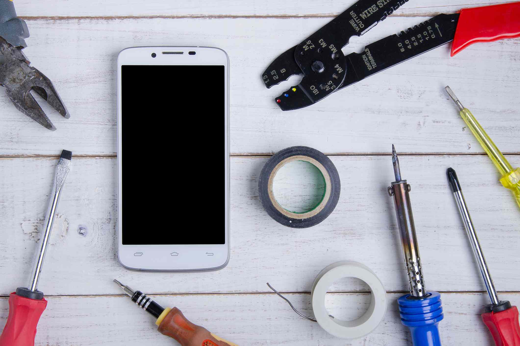 Top down view of a smartphone surrounded by the tools used to fix broken phones.