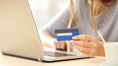 A person signing up for a YouTube Membership with a credit card and laptop.