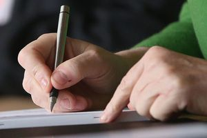 Close up of a man's hand holding a pen signing a contract