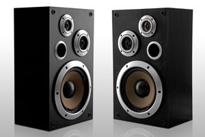 A pair of stereo speakers with exposed speaker cones