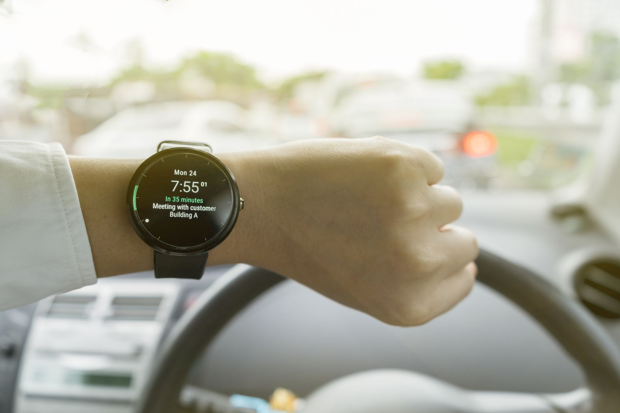 Man looking at smartwatch while driving