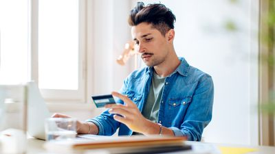 A man looking serious at his credit card while online shopping on his laptop.