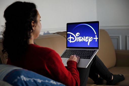 The Disney+ logo is displayed on the screen of a computer