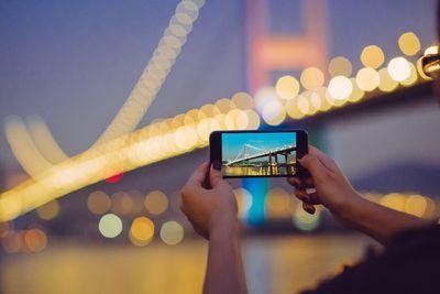 A camera phone held up to a bridge