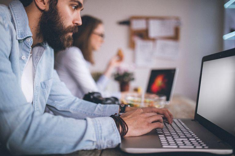 man editing images on laptop