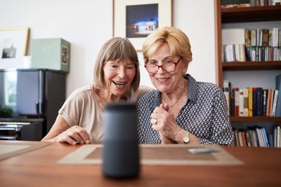 Two women sitting smiling at a smart speaker