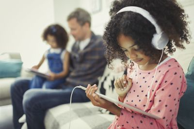 Girl with headphones using digital tablet on sofa