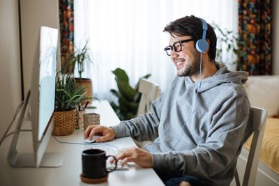 A man sitting at a computer desk with headphones on smiling at his computer monitor
