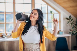 Girl listening to music on a Bluetooth speaker