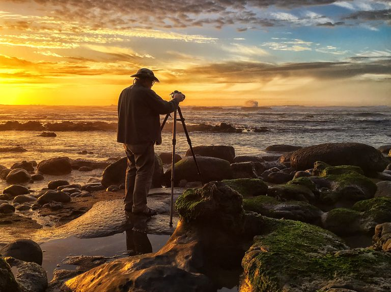 A photographer composing a sunset scene at a beach