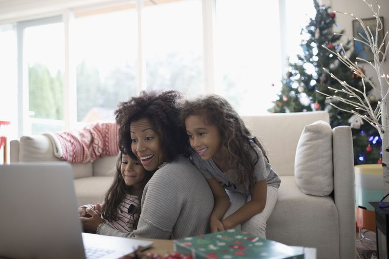 Smiling mother and daughters video chatting at laptop in Christmas living room