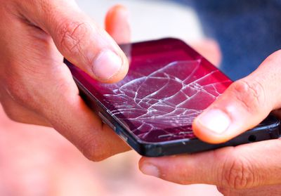 A broken smartphone with a cracked and flickering screen.