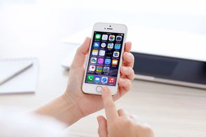 A hand holding an iPhone with iOS apps on it. Another hand is about to press the Home button.