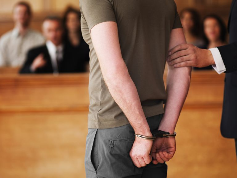 A man handcuffed in a courtroom.