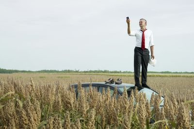Man standing on car holding cell phone