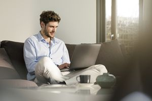 Telecommuter sitting on couch at home using laptop