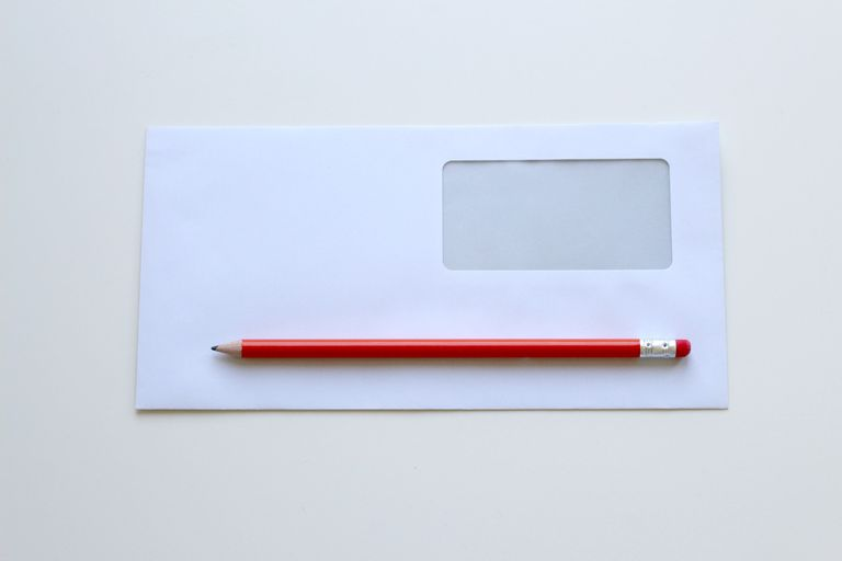 White envelope with a red pencil sitting on it.