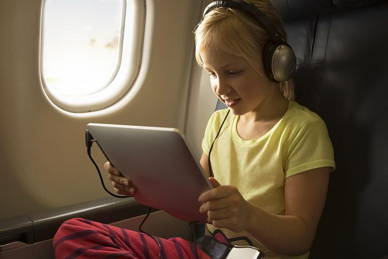 A girl watching a movie on a tablet computer in an airplane