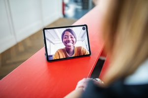 A woman on a video conferencing app displayed via a tablet