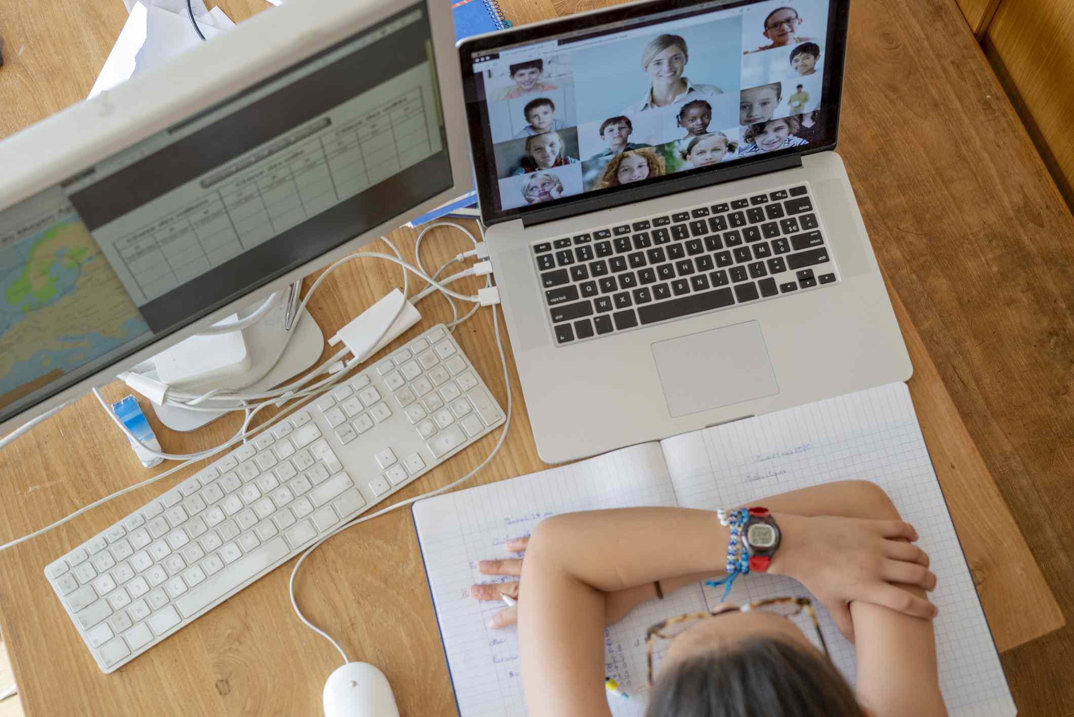 Overhead view of girl attending online school classes from home during coronavirus lockdown