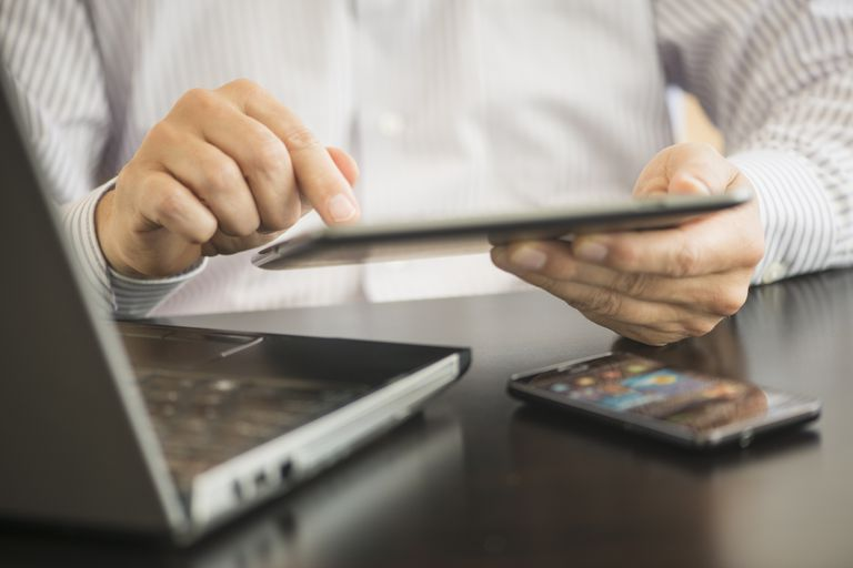 Close up of man using multiple mobile device - phone, table, and laptop