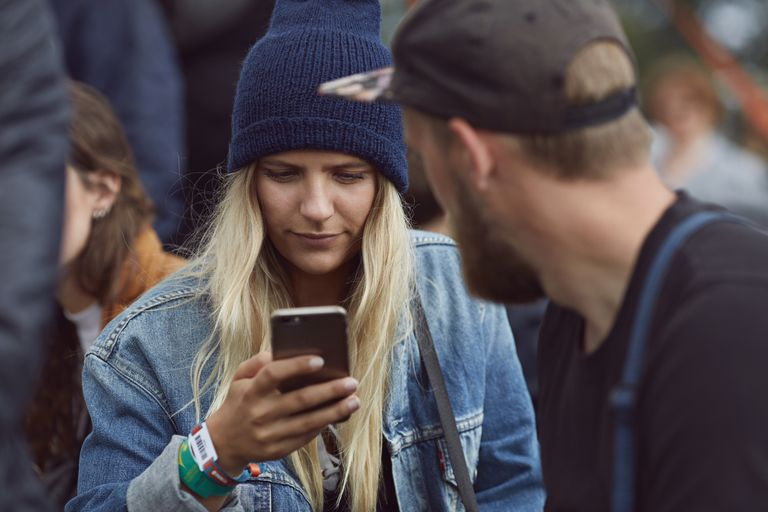 Woman checking email on crowded strewet
