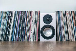 Vinyl records and loudspeaker box on hardwood floor