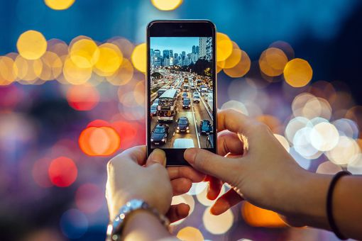 Person using an iphone to take a photo of traffic