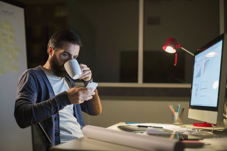 Man Drinking coffee and using iphone while working in an office