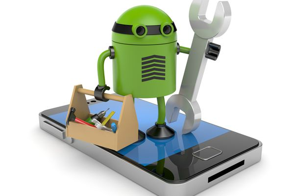 A droid holding a wrench and toolbox standing atop a smartphone