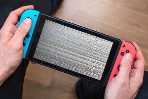 Hands holding a frozen Nintendo Switch console with static on its screen.