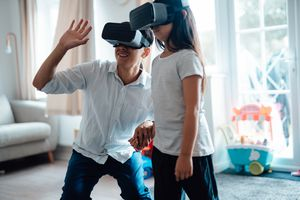 A man and his daughter using VR headsets together