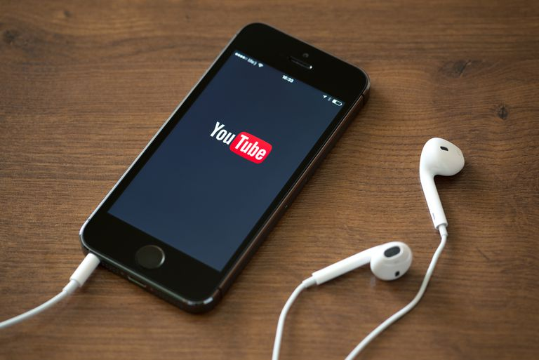 An image of the YouTube logo on a smartphone with a pair of headphones.
