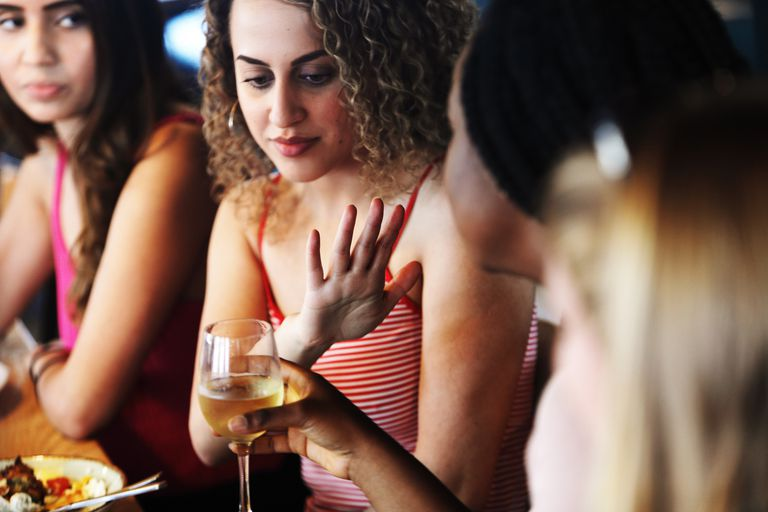 Young woman refusing wine in restaurant
