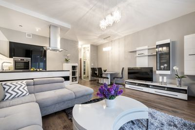 An open living room and kitchen area with furnishings and audio/video equipment