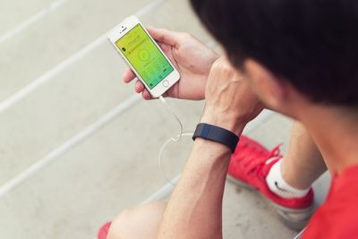 Jogger checking fitness app on smartphone