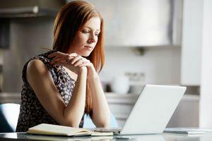 woman at laptop thinking