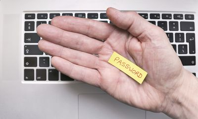 Hand holding a small piece of paper with the password written on it