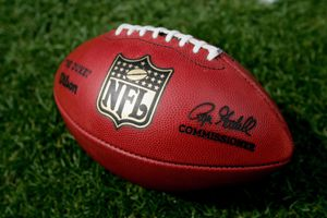 A close up of an official NFL football laying in grass.