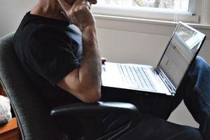 A man using a Windows laptop by a window.