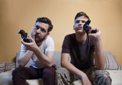 Two men sitting on a couch holding games controllers and looking fed up at an off-camera screen