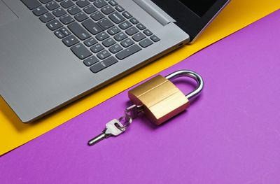 Windows 10 laptop on a yellow and purple surface with a locked lock.