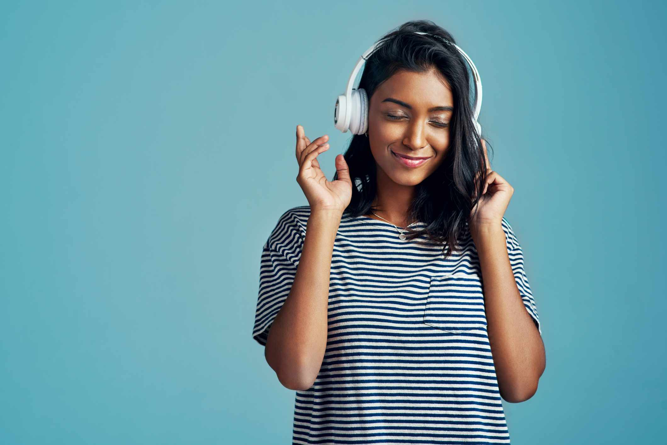 Someone listening to music through headphones, looking happy.